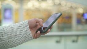 Tiro Handheld da mão masculina que enrola um telefone no fundo amarelo borrado vídeos de arquivo