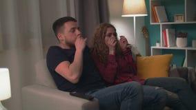 Tiro Handheld de pares novos no sofá tarde na noite que olha um filme de terror assustador