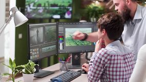 Tiro Handheld do editor video profissional em sua estação de trabalho filme