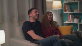 Tiro Handheld dos risos dos pares que olham uma comédia na sala de visitas na noite