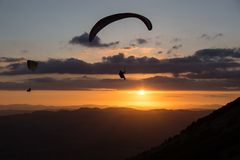 Tiro hermoso de dos siluetas del ala flexible que vuelan sobre Monte Cucco Umbria, Italia con puesta del sol en el fondo, con Fotografía de archivo libre de regalías