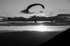 Tiro hermoso de dos siluetas del ala flexible que vuelan sobre Monte Cucco Umbria, Italia, con puesta del sol en el fondo Imagenes de archivo