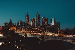 Tiro hermoso de una ciudad en la noche con rascacielos altos y un puente foto de archivo