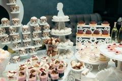 Tiro horizontal da tabela da sobremesa para o banquete de casamento coberto com os queques, os macarons e os outros doces fotografia de stock royalty free