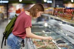 Tiro horizontal de ir femenino adolescente adorable a comprar las verduras congeladas, miradas en friedge mientras que hacen comp Imágenes de archivo libres de regalías