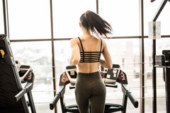 Tiro horizontal de la mujer que activa en la rueda de ardilla en el club de salud Elaboración femenina en un gimnasio que corre e Fotos de archivo libres de regalías