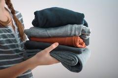 Tiro horizontal de un adolescente de la muchacha con dos trenzas que sostienen una pila de ropa, aislada en fondo gris Imagen de archivo