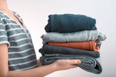 Tiro horizontal de un adolescente de la muchacha que sostiene una pila de ropa, aislada en fondo gris Fotografía de archivo libre de regalías