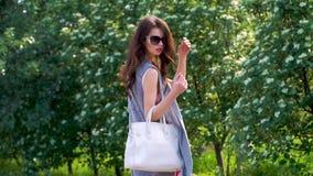 Tiro horizontal del aire libre de la mujer joven elegante que toma un paseo almacen de video