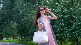 Tiro horizontal del aire libre de la mujer joven elegante que toma un paseo almacen de metraje de vídeo