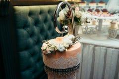 Tiro horizontal del primer del pastel de bodas anaranjado hermoso adornado con las flores y las gotas blancas y beige de la ejecu Fotografía de archivo
