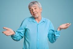 Tiro horizontal do homem maduro de cabelo cinzento hesitante com pele enrugada, ombros dos shruggs com a hesitação, vestida no az imagens de stock
