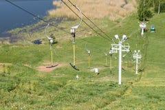 Tiro horizontal dos elevadores para esquiadores sobre o lago e o campo verde, fundo do verão Fotos de Stock Royalty Free