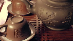 Tiro inclinable de las tazas de la arcilla y del pote del té en chaban Ceremonia de té del chino tradicional en la tabla de té almacen de video