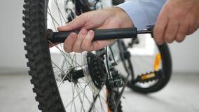 Tiro interior com ar de bombeamento do homem em pneus da bicicleta video estoque