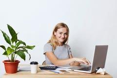 Tiro interior de la empresaria atractiva con la expresión feliz, tecleando en el ordenador portátil, estando ocupado con la fabri Fotos de archivo libres de regalías