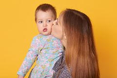 Tiro interior de la mujer blanda hermosa que detiene a su hija, besándola en mejilla La niña linda minúscula mira a un lado, l imagen de archivo