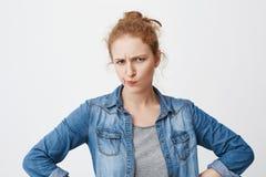 Tiro interior de los labios de estrabismo y plegables europeos sospechosos de la muchacha del pelirrojo que fruncen el ceño con l Fotografía de archivo libre de regalías