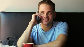 Tiro interior del hombre joven sonriente que se sienta y que habla en el teléfono móvil Individuo joven feliz en el caf? que habl almacen de video