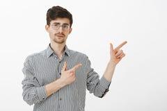 Tiro interior del individuo barbudo caucásico adulto inseguro con el bigote en vidrios redondos de moda, señalando a la derecha c Fotografía de archivo libre de regalías