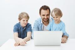 Tiro interior del niño rubio feliz positivo con el padre y el hermano que se sientan en la tabla, mirando la pantalla del ordenad Imágenes de archivo libres de regalías