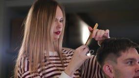Tiro interior del proceso de trabajo en barbería moderna Retrato de la vista lateral del hombre joven atractivo que consigue cort metrajes