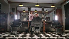 Tiro interior del proceso de trabajo en barbería moderna Retrato de la vista lateral del hombre joven atractivo que consigue cort almacen de metraje de vídeo