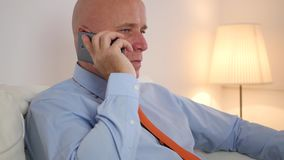 Tiro interno con l'uomo d'affari Making una telefonata facendo uso di Smartphone stock footage