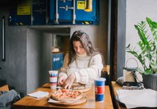 Tiro interno da mulher que come a pizza com bebida na manhã imagem de stock