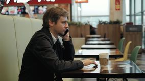 Tiro interno do homem novo de sorriso que senta-se na cafetaria e que fala no telefone celular Indivíduo novo feliz no café que f video estoque