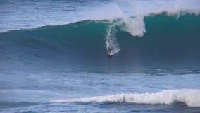 Tiro 4k lindo do surfista profissional que executa os conluios que montam ondas espumosas enormes do azul de turquesa no seascape video estoque