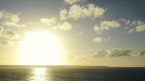 Tiro largo de um por do sol no timelapse sobre o oceano e nos penhascos no horizonte Zumbir progressivamente nos penhascos vídeos de arquivo
