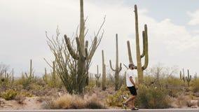 Tiro largo do movimento lento, homem novo do turista que anda ao longo de deserto grande surpreendente do cacto do Saguaro na est video estoque