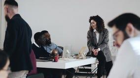 Tiro largo, mulher de negócio nova feliz do chefe que fala a dois colegas masculinos africanos na tabela moderna ocupada do local vídeos de arquivo