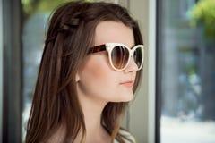 Tiro lateral da morena bonita nova com expressão segura, tentando em óculos de sol à moda ao comprar no ótico fotografia de stock royalty free