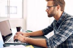 Tiro lateral de um homem de negócios que trabalha em seu portátil Imagens de Stock Royalty Free