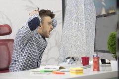 Tiro lateral del perfil del empresario moreno joven frustrado, gritando en su ordenador portátil en oficina y calambres los docum foto de archivo