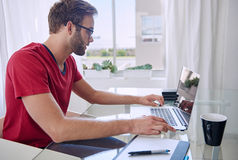 Tiro lateral do estudante que trabalha na mesa da casa Imagens de Stock Royalty Free