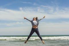 Tiro lleno de un adolescente sonriente que salta en la costa del bea Fotografía de archivo libre de regalías