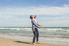 Tiro lleno de un adolescente sonriente que salta en la costa del bea Foto de archivo libre de regalías