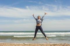 Tiro lleno de un adolescente sonriente que salta en la costa del bea Fotos de archivo