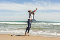 Tiro lleno de un adolescente sonriente que salta en la costa del bea Fotos de archivo libres de regalías