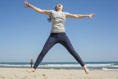 Tiro lleno de un adolescente sonriente que salta en la playa en DA clara Foto de archivo libre de regalías