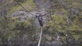 Tiro lleno del cuerpo de una mujer joven que cruza un puente del alambre sobre el río de Nevis, Escocia metrajes