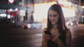 Tiro médio bonito da mulher local europeia feliz que olha em torno de usar o app do smartphone no sorriso escuro da rua de New Yo filme