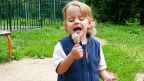 Tiro médio da criança que come o gelado video estoque