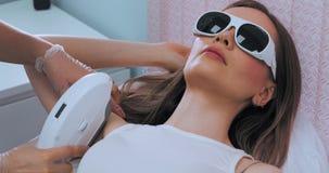 Tiro médio da mulher moreno magro nova quando procedimento de remoção do cabelo de axila do laser Conceito indesejável do cabelo video estoque