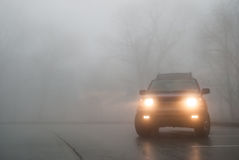 Tiro médio de luzes de SUV na névoa Fotografia de Stock Royalty Free