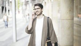 Tiro médio de um homem de negócios que fala seu telefone esperto na rua e que olha a câmera Foto de Stock Royalty Free