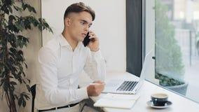 Tiro médio do homem de negócios novo concentrado que toma notas no caderno ao falar no telefone durante a ruptura de café filme